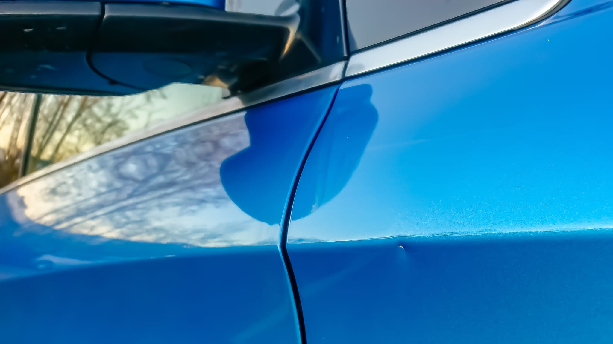 A small dent in the fender of a blue metallic car
