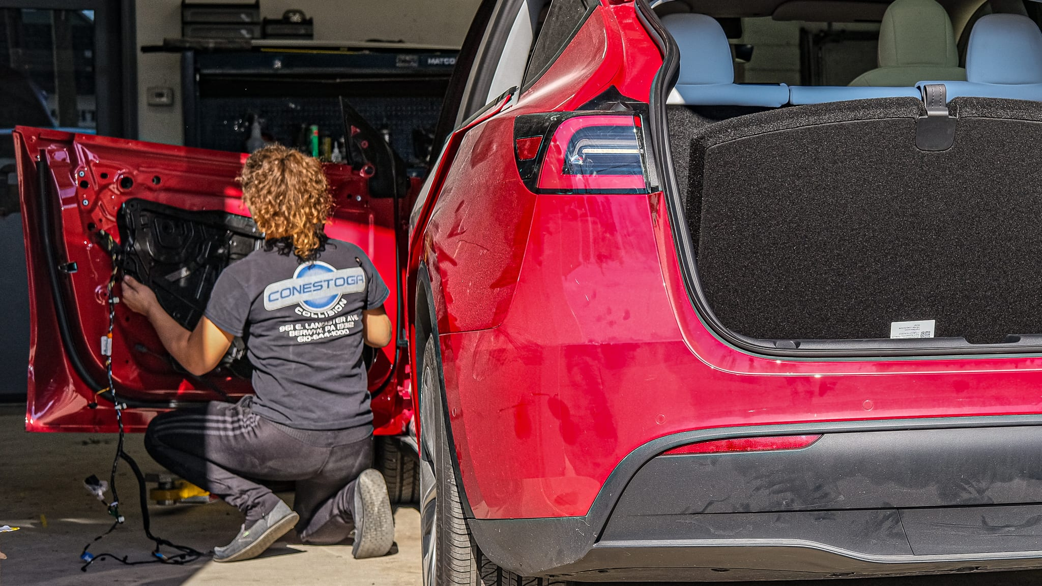 Technician Sydney disassembling a Tesla, cataloging every part along the way.