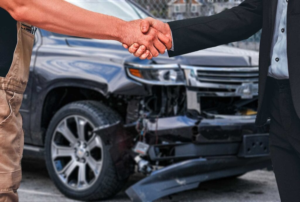 Mechanic And Professionally Dressed Customer Shake Hands In Front Of Damaged SUV