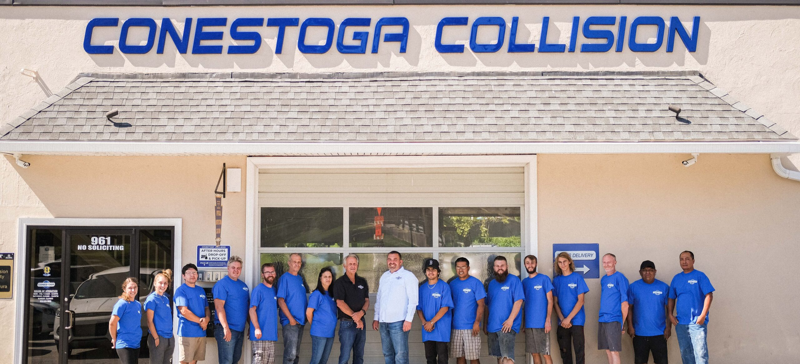 Owners Max Keller and Pete Hutchinson stand with 15 team members outside the front of Conestoga Collision